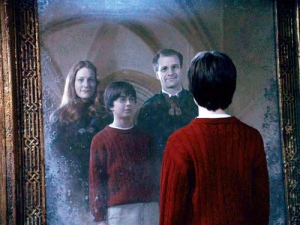 "The movie ""Harry Potter and the Sorcerer's Stone"", (alt.: Harry Potter and the Philosopher's Stone), directed by Chris Columbus, based on the novel by J.K. Rowling.  Seen here, Daniel Radcliffe as Harry Potter gazing into he Mirror of Erised, seeing his mother, Lily Potter (played by Geraldine Somerville) and father, James Potter (played by Adrian Rawlins).  Initial world premiere (London) November 4, 2001.  Screen capture. © 2001 Warner Bros. Credit: © 2001 Warner Bros. / Flickr / Courtesy Pikturz.  Image intended only for use to help promote the film, in an editorial, non-commercial context."